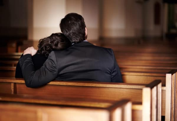 Rearview of a man comforting a woman at a funeral